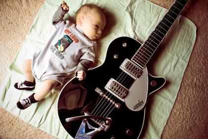 Малыш лежит рядом с гитарой (приучаем к музыке)